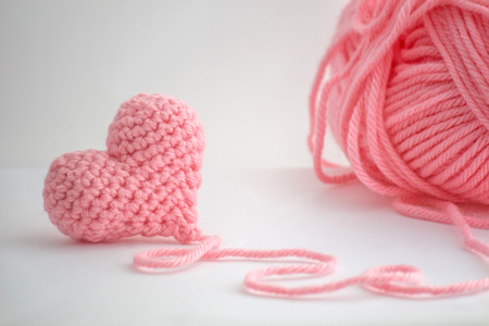 Photo for Adorable little heart crocheted by hand. Made with a thread of a thick bulky wool thread. The thread is not cut and still attached to the heart. - Royalty Free Image