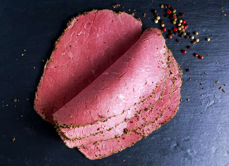 Photo for Peppered roast beef pastrami slices on paper with grains of coloured pepper - Royalty Free Image