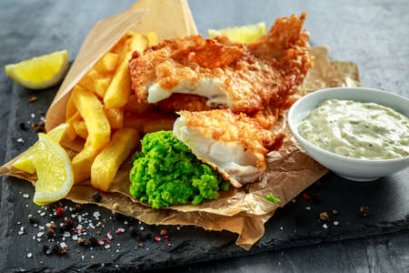 Foto de British Traditional Fish and chips with mashed peas, tartar sauce on crumpled paper. - Imagen libre de derechos