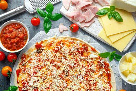Foto de Ready to cook pizza with tomatoes sauce, cheese on Parchment paper. - Imagen libre de derechos