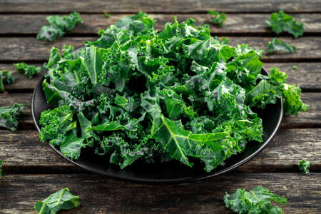 Photo for Fresh green healthy superfood vegetable kale leaves in a black plate on wooden rustic table - Royalty Free Image