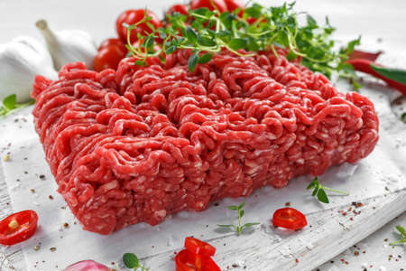 Foto de Fresh Raw Beef Minced Meat with salt, pepper, chilli and fresh thyme on white board. - Imagen libre de derechos