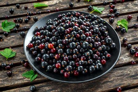 Photo pour Fresh Juicy black currants in a plate on wooden rustic table - image libre de droit
