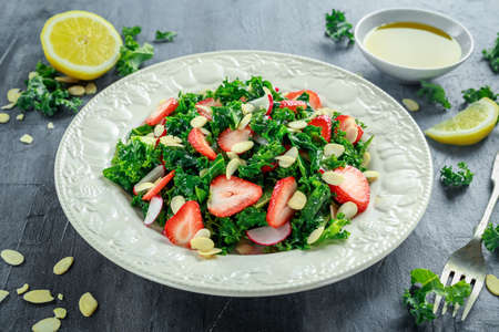 Photo pour Healthy kale salad with strawberries and almond in a white plate - image libre de droit