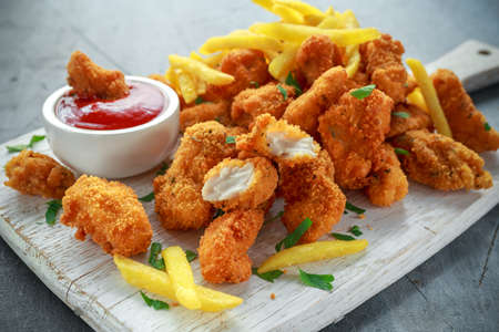 Photo for Fried crispy chicken nuggets with french fries and ketchup on white board - Royalty Free Image