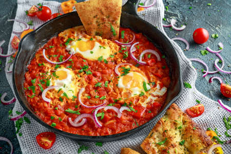 Photo pour Tasty Breakfast Shakshuka in a Iron Pan. Fried eggs with tomatoes, red, yellow peppers, onion, parsley, Pita bread and herbs. Healthy Food - image libre de droit