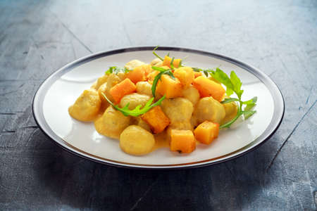 Photo for Homemade Butternut squash gnocchi with wild rocket in a plate - Royalty Free Image