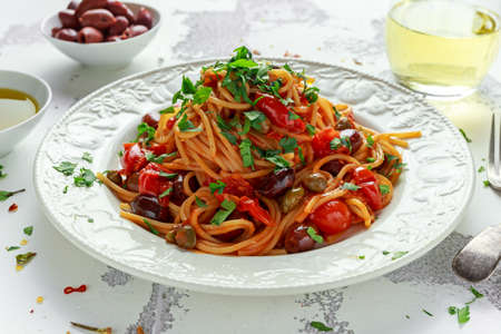 Photo for Vegetarian Italian Pasta Alla Puttanesca with garlic, olives, capers with on white plate. - Royalty Free Image