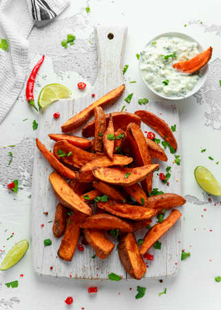 Photo for Healthy Homemade Baked Orange Sweet Potato wedges with fresh cream dip sauce, herbs, salt and pepper. - Royalty Free Image