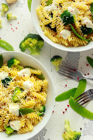 Photo for Pasta with green vegetables broccoli, Mange tout and creamy sauce in white plate - Royalty Free Image