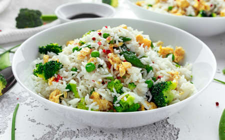 Foto de Fried rice with vegetables, broccoli, peas and eggs in a white bowl. healthy food - Imagen libre de derechos