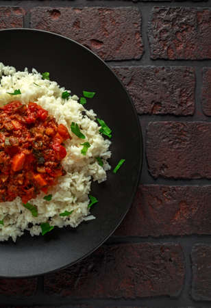 Foto de Homemade beef mince and vegetable casserole served with rice on black plate. - Imagen libre de derechos