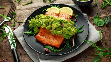 Photo for Oven cooked salmon steak, fillet with avocado salsa and green on black plate. wooden table. healthy food - Royalty Free Image