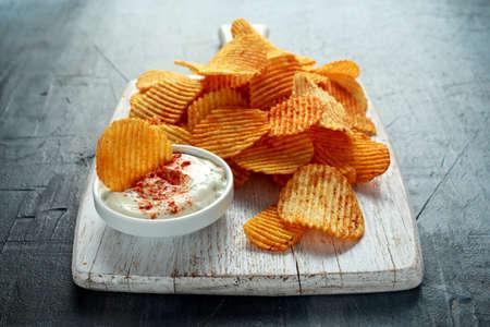 Foto de Potato chips, snack crisps with red paprika and white dip sauce on white board. - Imagen libre de derechos