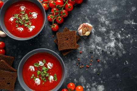 Photo pour Tomato and fresh basil soup with garlic, cracked papper corns, served with cream and sourdough bread - image libre de droit