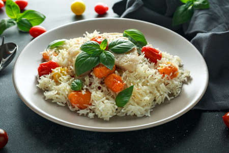 Foto de Steamed cod fish with rice and cherry mix tomatoes and basil herbs in a plate - Imagen libre de derechos