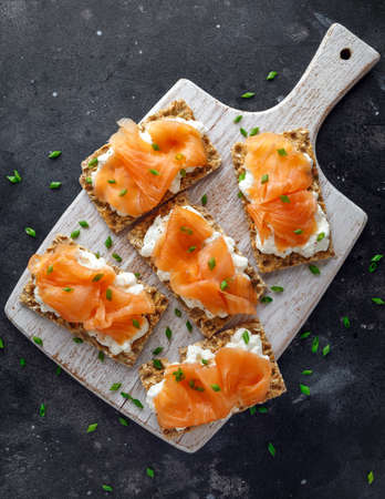 Photo pour Homemade Crispbread toast with Smoked Salmon and soft chees, chives on white board - image libre de droit
