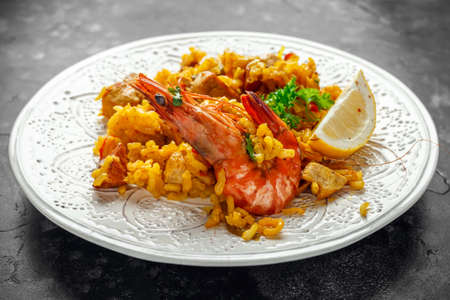 Photo pour Traditional paella on white plate with chicken, prawns, spicy chorizo, lemon and glass of white wine. - image libre de droit