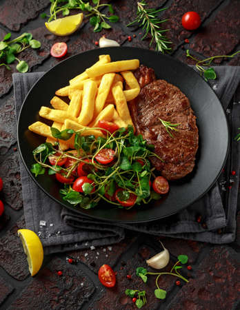 Photo pour Grilled sirloin steak with potato fries and vegetables, tomato salad in a black plate. rustic table - image libre de droit