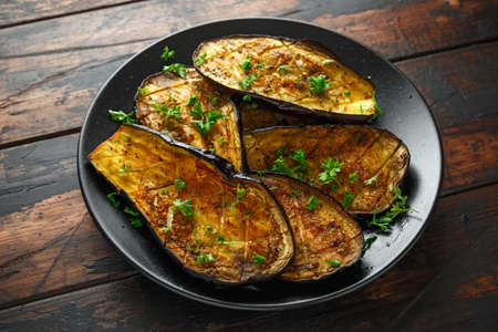 Photo for Healthy vegeterain Oven baked aubergines, Eggplant with parsley and herbs in a black plate - Royalty Free Image