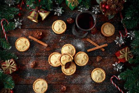 Foto de British Christmas mince pies with decoration, gifts, green tree branch on wooden rustic table - Imagen libre de derechos