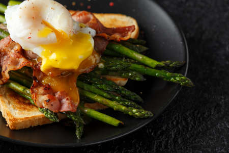 Photo for Benedict poached Duck egg with crispy bacon and fried asparagus on toasts for breakfast - Royalty Free Image
