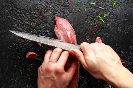 Photo pour Butchers hands ready to cut with a knife raw pork tenderloin fillet - image libre de droit