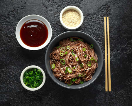 Photo pour Soba noodles, buckwheat on a black bowl, with spring onion and sesame seeds. Traditional Japanese food. - image libre de droit