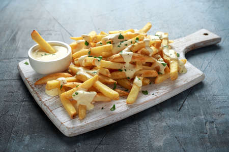 Photo pour Homemade Baked Potato Fries with cheese sauce on white wooden board - image libre de droit