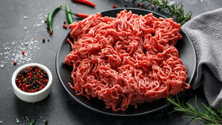 Foto de Fresh Raw mince, Minced beef, ground meat with herbs and spices on black plate - Imagen libre de derechos