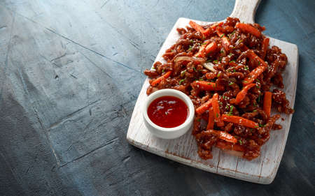 Photo for Crispy shredded beef with carrots and sweet chilli sauce on white wooden board. Chinese takeaway food - Royalty Free Image