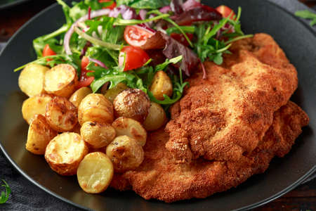 Photo for Homemade breaded pork schnitzel with roast potato and vegetables - Royalty Free Image