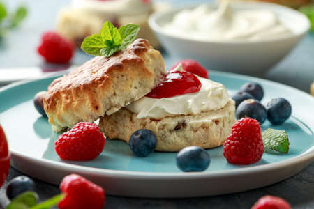 Foto de Classic English scones with clotted cream, strawberries jam and other fruit - Imagen libre de derechos