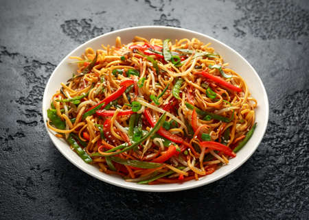 Photo for Chow mein, noodles and vegetables dish with wooden chopsticks - Royalty Free Image