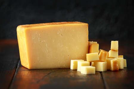 Foto de Bitesize Sliced smoked cheddar cheese on rustic wooden background - Imagen libre de derechos