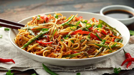 Photo for Chow mein, noodles and vegetables dish with wooden chopsticks. - Royalty Free Image