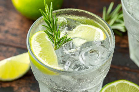 Foto de Gin and Tonic Alcohol drink with Lime, Rosemary and ice on wooden table. - Imagen libre de derechos