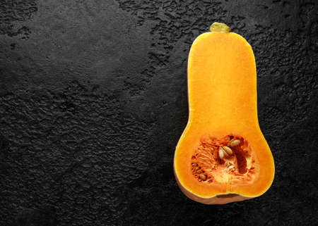 Photo for Fresh Butternut squash slice on black rustic background. - Royalty Free Image