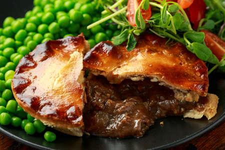 Foto de Beef steak pies with rich onion gravy served with sweet peas and salad - Imagen libre de derechos