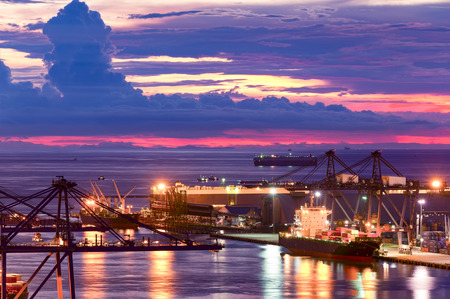 Background for cranes and industrial cargo ships in port at twilight.
