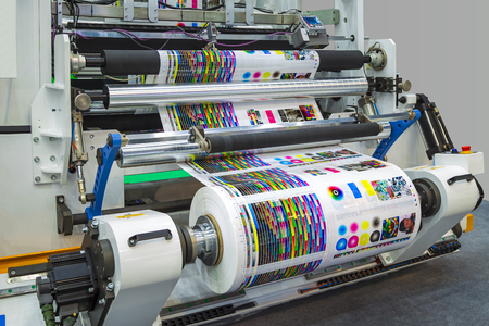 Foto de Large offset printing press or magazine running a long roll off paper in production line of industrial printer machine. - Imagen libre de derechos