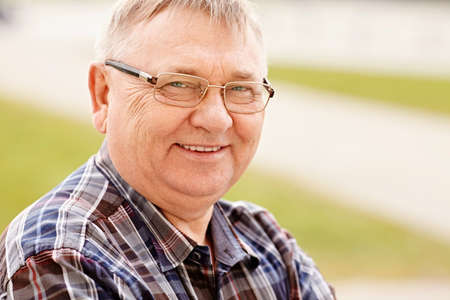 Photo for Close up outdoors portrait of smiling middle aged man in glasses and cheered shirt - Royalty Free Image