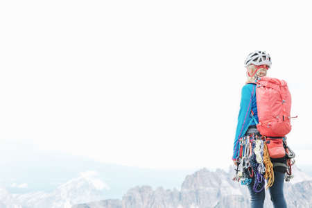Female mountaineer with trad climbing rack including backpack, helmet, chalk bag, harness with spring-loaded cams, nuts, quickdraws, slings and carabiners enjoying view to valley, copy space