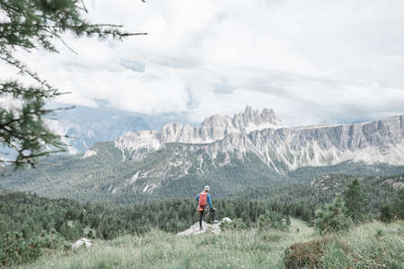 Female mountaineer with backpack, helmet and harness with climbing gear enjoying stunning view to mountains before ascent during summer day in Dolomite Alps - mountaineering or sport climbing concept