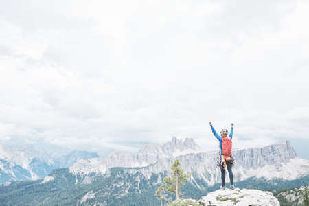 Female mountaineer with backpack, helmet and harness with climbing gear raising her hands celebrating successful climb during summer day in Dolomite Alps - mountaineering or sport climbing concept