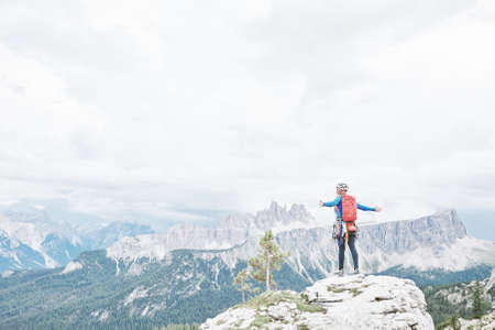 Female mountaineer with backpack, helmet and harness with climbing gear standing on top of mountain with arms outstretched and enjoying view to valley and peaks in Dolomite Alps - freedom concept