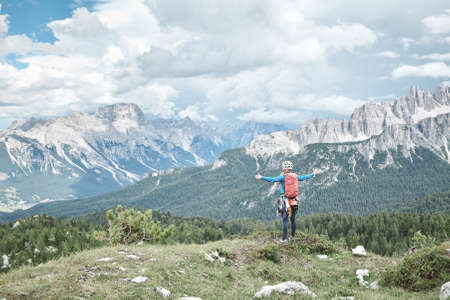 Female mountaineer with backpack, helmet and harness with climbing gear standing with arms outstretched and enjoying view to valley and peaks in Dolomite Alps - adventure and freedom concept