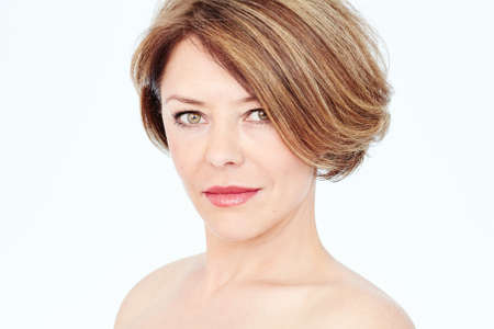 Foto de Close up portrait of beautiful middle aged woman with short brown hair, fresh makeup, naked shoulders and neck over white background - mature beauty, skin care or anti age concept - Imagen libre de derechos