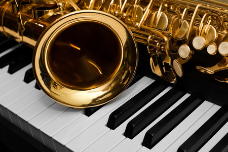 Photo for Fragment of the saxophone lying on the piano keys - Royalty Free Image