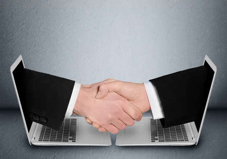 Photo for Business people handshake through computer - Royalty Free Image